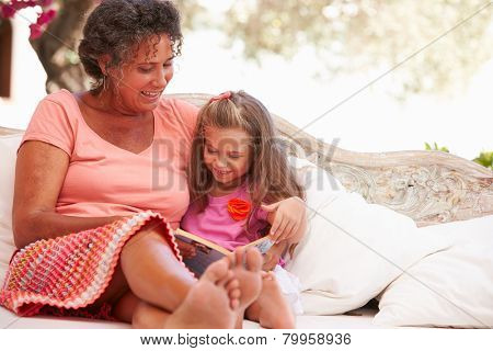 Grandmother With Granddaughter Reading Book In Garden