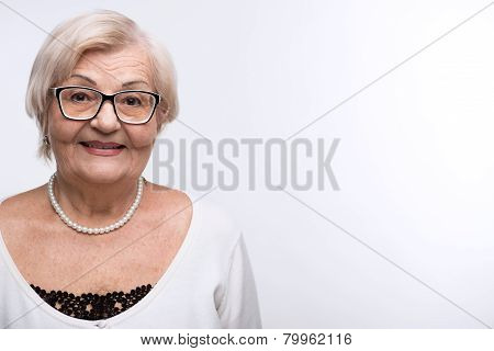 Curious granny looking through her glasses
