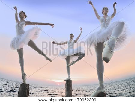 Three dancers standing on stilts