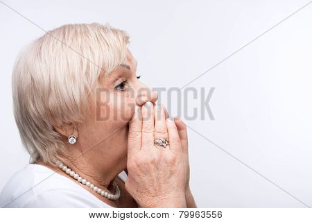 Elderly lady shouting putting hands by her mouth