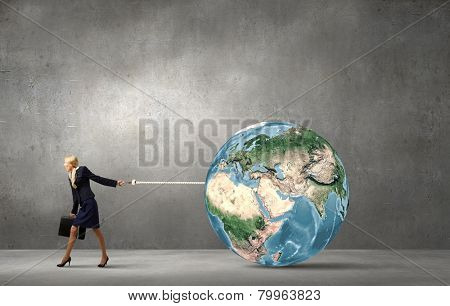 Young businesswoman holding Earth planet on lead. Elements of this image are furnished by NASA