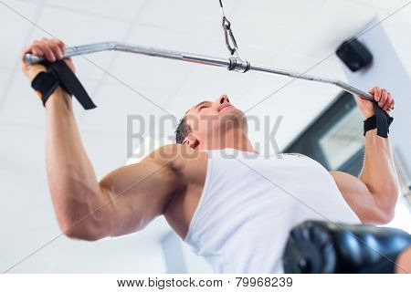 Man doing bodybuilding sport by exercising lifting dumbbells in fitness club or gym