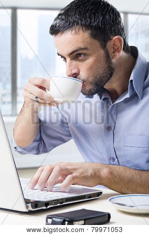 Young Attractive Businessman Working On Computer Laptop Drinking Cup Of Coffee Cup Sitting At Office