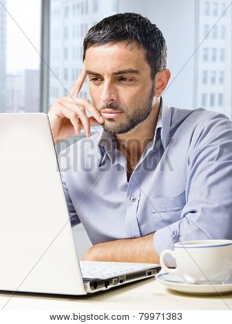 Attractive Businessman Working On Computer At Office Desk In Front Of Skyscraper Window