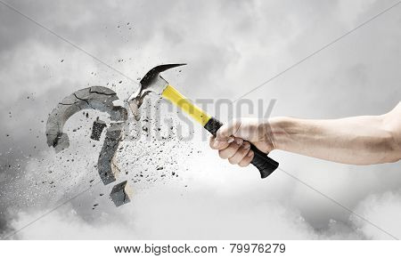 Close up of hammer in human hand breaking stone question mark