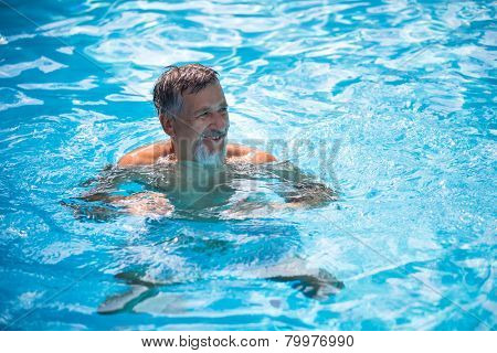 Senior man in his home swimming pool, enjoying the deserved retirement