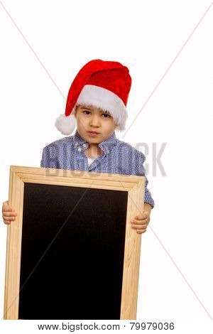 little boy with santa hat holding a blackboard symbol of christmas, childhood, marketing