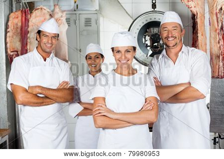 Portrait of mature female butcher with confident team in butchery