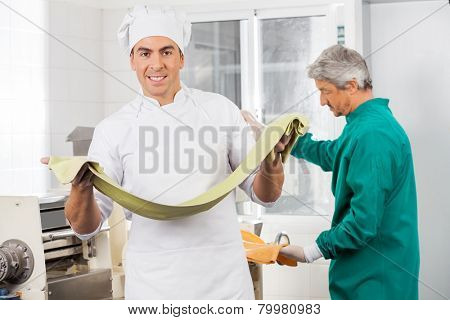 Portrait of confident male chef holding pasta sheet with colleague working in background at commercial kitchen