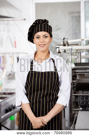 Portrait of confident female chef standing in commercial kitchen