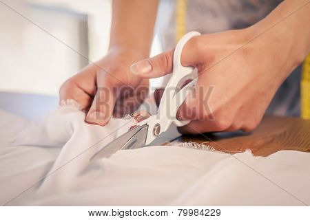 Close up of sewer hands cutting cloth with scissors