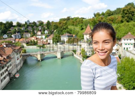 Tourist relaxing in Bern during Switzerland travel. Woman traveler visiting tourists attractions and landmarks in Berne. Mixed race Asian Caucasian female model on the Nydegg Bridge by the Aare river.