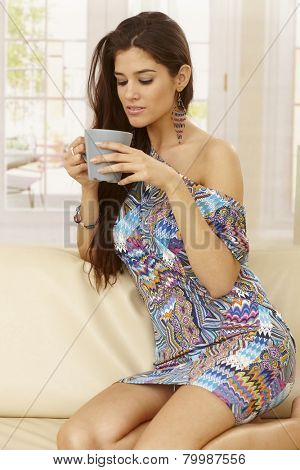 Pretty young woman kneeling on sofa at home, drinking tea.