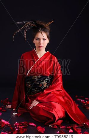 The girl in native costume of japanese geisha, against the black background