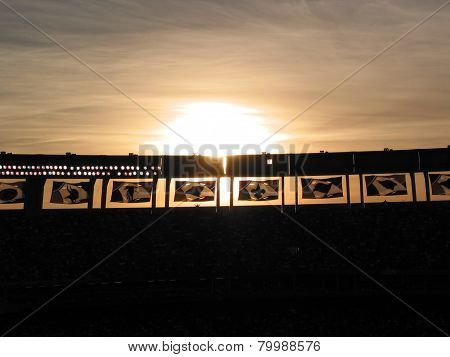 Sun setting behind Qualcomm Stadium Football Team Banners