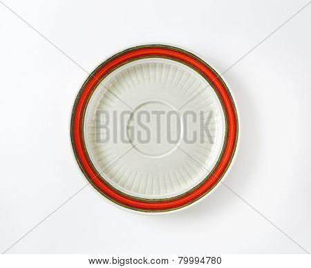 white saucer with red rim on white background