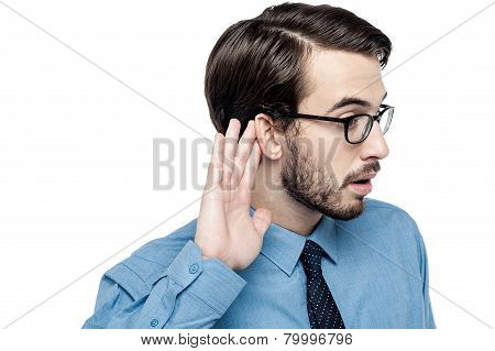 Corporate Man Listening With Hand On Ear