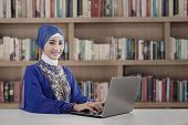 image of muslimah  - Muslim student typing on laptop shot in library - JPG