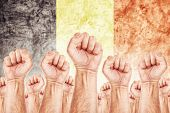 picture of labourer  - Belgium Labour movement workers union strike concept with male fists raised in the air fighting for their rights Belgium national flag in out of focus background - JPG