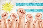 foto of labourer  - Uruguay Labour movement workers union strike concept with male fists raised in the air fighting for their rights Uruguayan national flag in out of focus background - JPG
