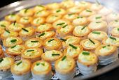 foto of buffet  - Tray of savory vol au vent appetizers with crisp gplden pastry cases filled with a creamy filling topped with chives on a buffet table - JPG