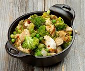 picture of stew  - Delicious Homemade Chicken Stew with Green Pea Broccoli and Bell Pepper in Black Saucepan isolated on Rustic Wooden background - JPG