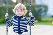 picture of swings  - Cute blond boy having fun and swinging on outdoor playground - JPG