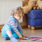 image of indoor games  - Little cute blond boy playing with puzzle game at home. Kid having fun indoors. child development concept