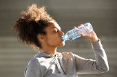 picture of bottle water  - Close up portrait of an attractive young woman drinking water from bottle - JPG