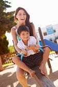 stock photo of seesaw  - Mother And Son Having Fun On Seesaw In Playground - JPG
