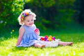 image of baby easter  - Cute little toddler girl with curly hair wearing a blue summer dress having fun during Easter egg hunt relaxing in the garden on a sunny spring day - JPG
