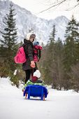 stock photo of toboggan  - Young mother pulling her small child through winter snow on a toboggan turning to check that the child is safe in a mountain pine forest.