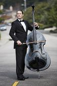 image of double-bass  - man in tuxedo playing the double bass in the middle of the street - JPG