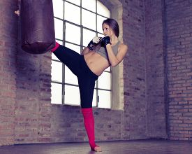 image of heavy bag  - young woman kicking the heavy bag in the gym - JPG