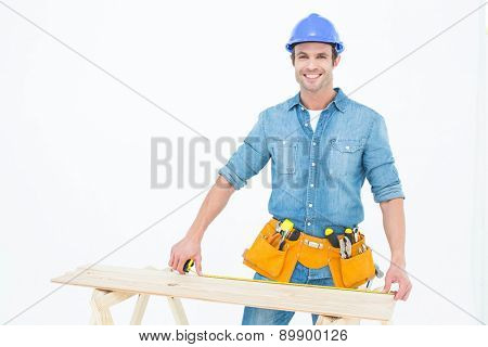 Portrait of happy male carpenter measuring wooden plank over white background