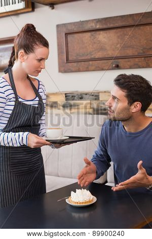 Waitress bringing man coffee and tart at the cafe