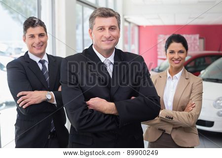 Smiling business team standing with arms crossed at new car showroom