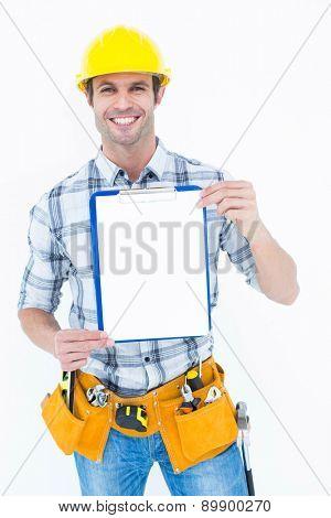 Portrait of confident carpenter holding clip board over white background