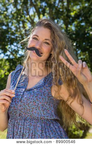 Pretty blonde with fake mustache on a summers day