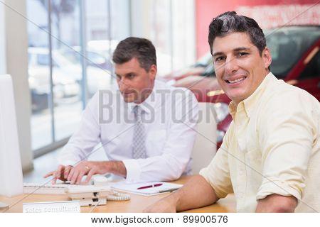 Smiling customer looking at camera at new car showroom