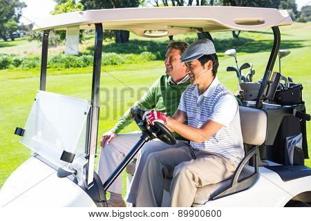 Golfing friends laughing together in their golf buggy at the golf course
