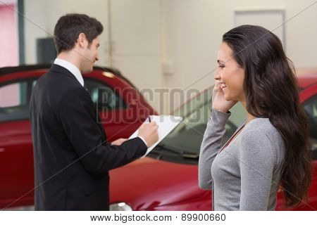 Smiling woman calling someone with her mobile phone at new car showroom