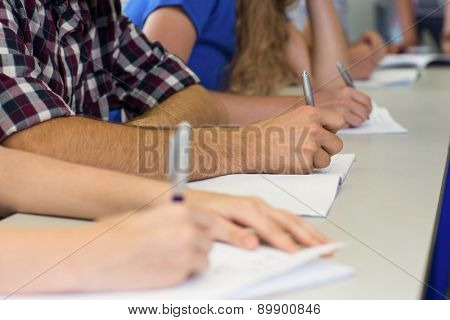 Side view mid section of students writing notes in classroom