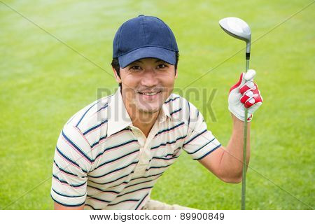 Crouching golfer smiling at camera and holding club at the golf course