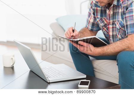 A man taking notes notebook sitting on a sofa at home in the living room