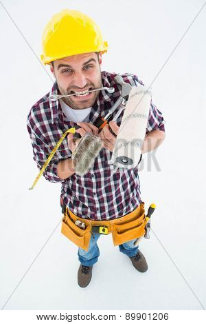 High angle view of frustrated handyman holding various tools on white background