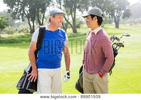 Golfing friends smiling and holding clubs at golf course
