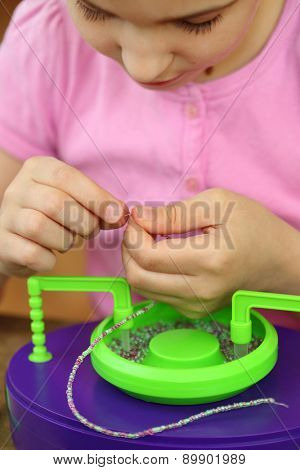 Girl bowing head collects shallow color beads