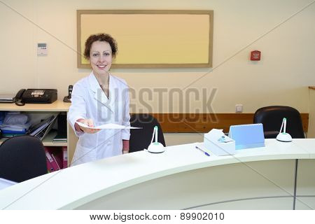 Medical worker in white coat holds out a sheet of paper at the reception