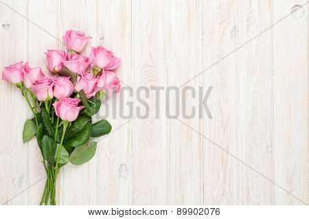 Pink roses bouquet over wooden table. Top view with copy space